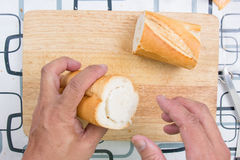 Hand with knife penetrate bread Stock Images
