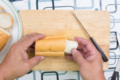 Hand with knife penetrate bread Royalty Free Stock Photo