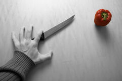 Hand, Knife and Red Pepper. A Hand, Knife and Red Pepper Royalty Free Stock Images