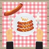 Hand with a knife and sausages on a plate. Royalty Free Stock Images