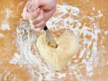 Hand with knife struck heart of dough Stock Images