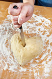 Hand with knife struck heart of dough Stock Image