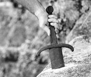 Knight who extracts Excalibur the legendary sword in the stone. Hand of the knight who extracts Excalibur the legendary sword in the stone Royalty Free Stock Photo