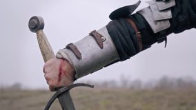 The hand of the knight woman in the wounds that holds the sword. Female hand in medieval armor holds a sword stock video footage