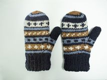 Hand knit gloves with blue gold and white pattern royalty free stock photos