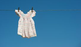 Hand knitted baby dress drying on line. royalty free stock photography