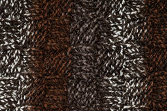 Hand knitted brown background. Close-up of hand knitted striped fabric, made with acrylic and wool mix chunky yarn. Great for craft background royalty free stock images