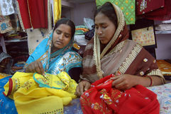 Hand knitted garments. Two Indian women are making embroidery designs on garments in a craft fair Royalty Free Stock Images