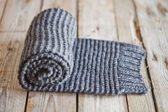 Hand knitted gray scarf. Hand knitted gray scarf on wooden background royalty free stock photography