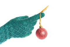 Hand in knitted green gloves with red Christmas ball isolated Stock Photography