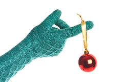 Hand in knitted green gloves with red Christmas ball isolated Stock Photos