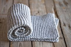 Hand knitted grey scarf. On wooden background stock images