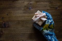 Hand in knitted mittens holding present, rustic wood background Stock Photography