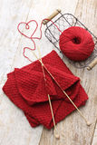 Hand knitted red scarf and heart shaped thread stock photos