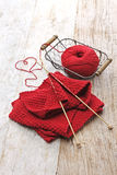 Hand knitted red scarf and heart shaped thread Royalty Free Stock Photo