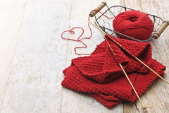 Hand knitted red scarf and heart shaped thread Royalty Free Stock Images
