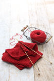 Hand knitted red scarf, yarn ball and knitting needles Stock Image