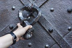 Hand knock on the door. Old medieval black doorwith metal knocker Royalty Free Stock Photo