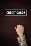 Hand is knocking on Credit Cards door Stock Images