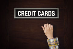 Hand is knocking on Credit Cards door Royalty Free Stock Photography
