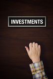 Hand is knocking on Investments door Stock Photo