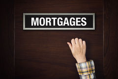 Hand is knocking on Mortgages door Royalty Free Stock Photos