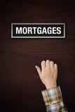 Hand is knocking on Mortgages door. Female hand is knocking on Mortgages door, conceptual image Stock Photos