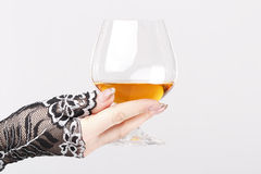 Hand hold glass with brandy. Hand in lace gloves with manicure hold glass with brandy or cognac Stock Photo