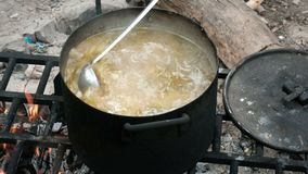 A hand with a ladle mixes the ingredients in boiling soup. Cooking in a large pot in nature. Food for hike travelers. Camp tourist