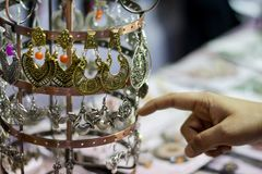 Hand of a lady selecting ear rings metal junk jewellery at a shop.  stock photos