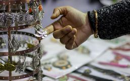 Hand of a lady selecting ear rings metal junk jewellery at a shop.  stock photography