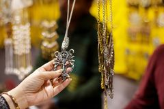 Hand of a lady selecting necklace chain metal junk jewellery at a shop.  royalty free stock image