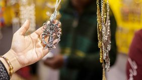 Hand of a lady selecting necklace chain metal junk jewellery at a shop.  stock photography