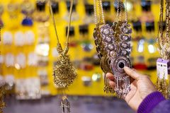 Hand of a lady selecting necklace chain metal junk jewellery at a shop.  stock photo