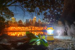 Hand lantern on the background of Midtown Atlanta at dusk. Luminous hand lantern standing on the ground of Piedmont Park on the background of Midtown Atlanta at Stock Photo