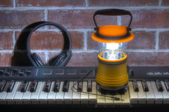 Hand lantern on keyboard with headphones, HDR Stock Image