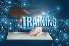 Hand from laptop clicks on the word training. stock image