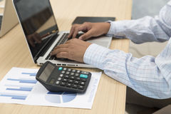 Hand on laptop computer with digital tablet, calculator and docu. Ment for use as working concept Royalty Free Stock Images