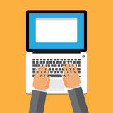 Hand on laptop keyboard with blank screen monitor Stock Photography