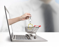 Hand from laptop screen taking house key in shopping cart Stock Photos