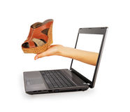 Hand of a laptop stretches female sandals Royalty Free Stock Photography