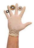 Hand in latex glove with used gears Royalty Free Stock Image