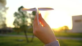 Hand launches paper airplane against sunset background. Slow motion stock video footage