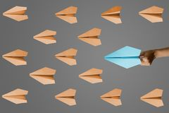 Paper planes on gray background. Hand launches a paper plane to towards other aircrafts on gray background stock images