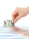 Hand launching money ship Stock Images