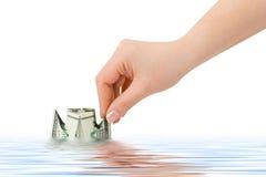 Hand launching money ship Stock Photo
