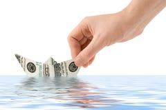 Hand launching money ship Royalty Free Stock Photo