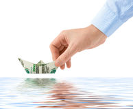 Hand launching money ship Stock Image