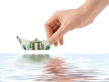 Hand launching money ship Stock Photos