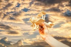 Hand launching wood airplane and orange sky at time sunset.  Royalty Free Stock Image